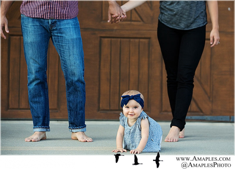 baby girl crawling between parents bare feet