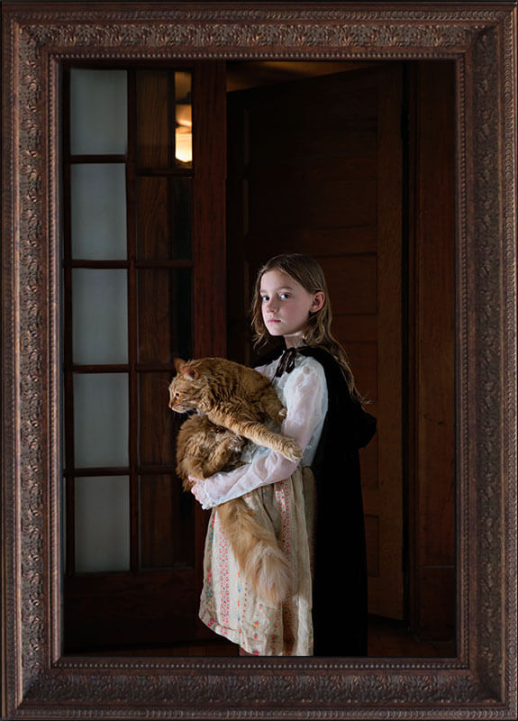 fine art portrait of little girl holding large orange cat